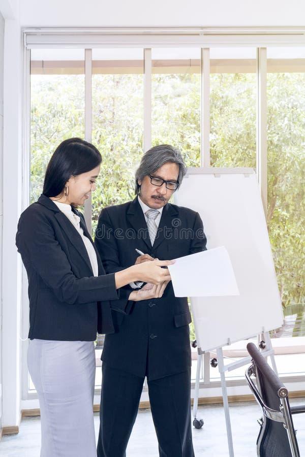 Ungt affärskvinnatecken ett dokument och ett möte med den höga chefen royaltyfri bild