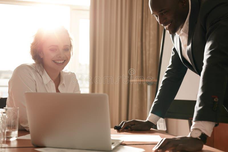 Ungt affärslag som tillsammans arbetar på bärbara datorn royaltyfri bild