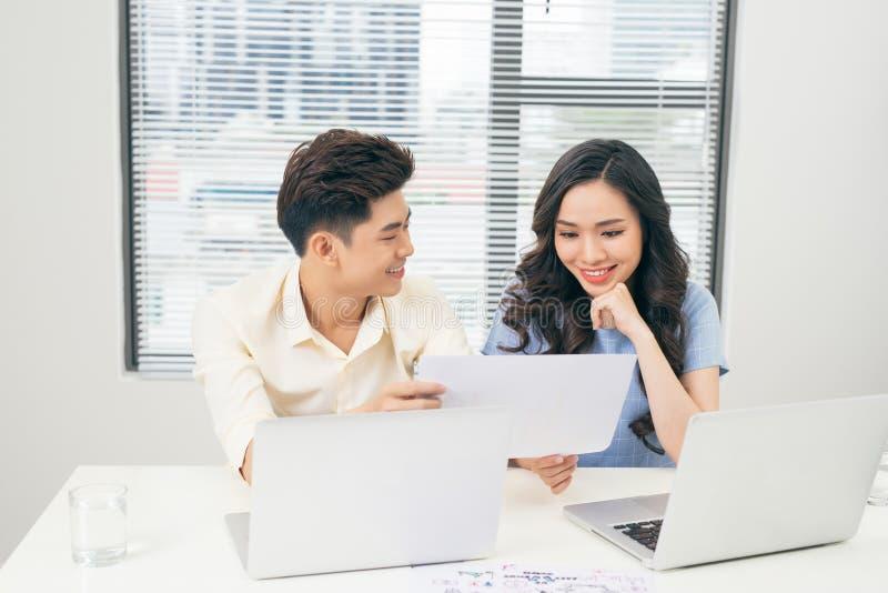Ungt affärslag som tillsammans arbetar på en bärbar dator, en man och en kvinna royaltyfria bilder