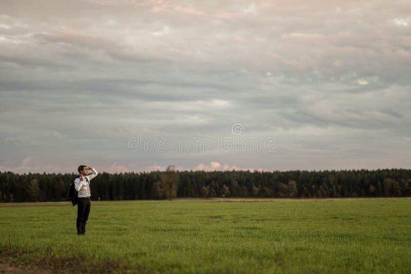 Ungt affärsmananseende i den gröna ängen som in ser till ett avstånd arkivfoto