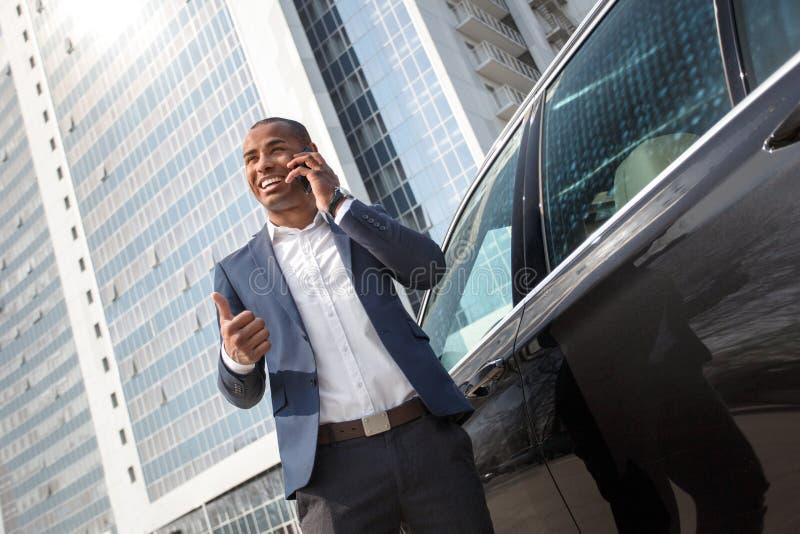 Ungt affärsmananseende nära för påringningvisning för bil den svarande tummen upp gladlynt nedersta sikt royaltyfri bild
