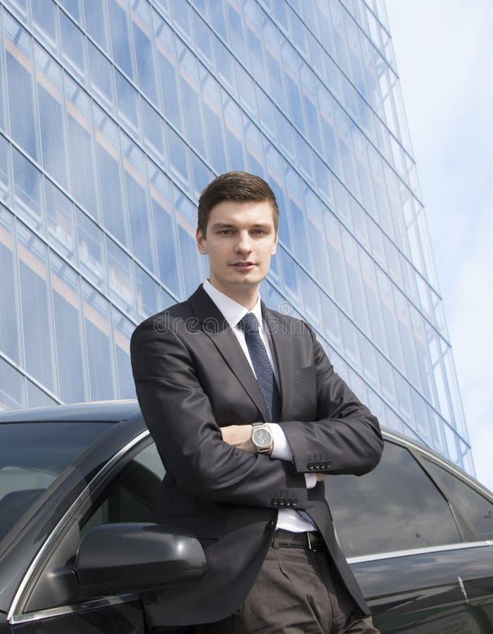 Ungt affärsmananseende nära hans bil arkivbilder