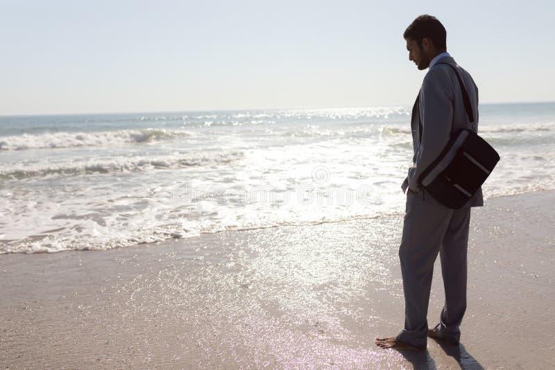 Ungt affärsmananseende på stranden royaltyfri fotografi