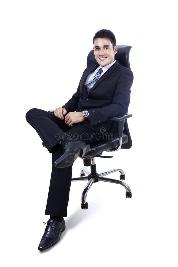 Ungt affärsmansammanträde på isolerad stol - fotografering för bildbyråer