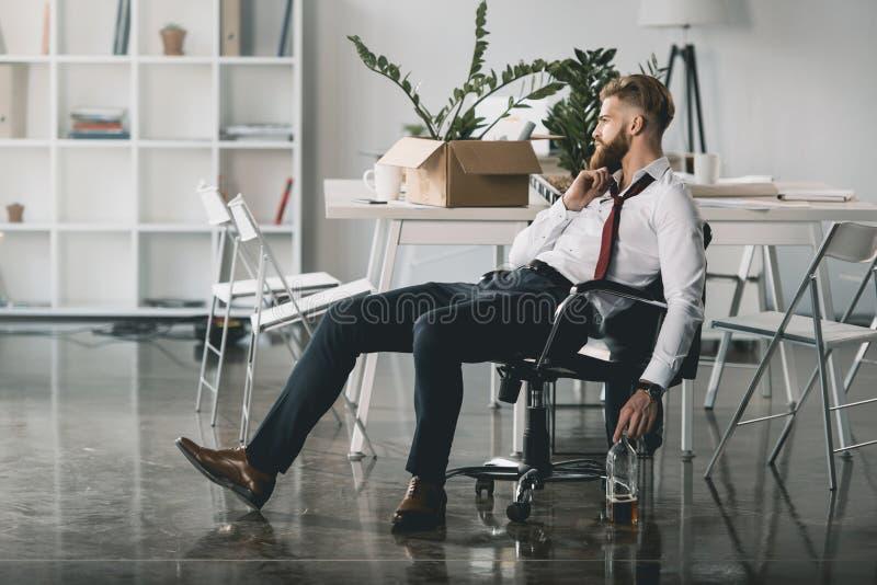 Ungt affärsmansammanträde på stol med flaskan av whisky i regeringsställning arkivfoton