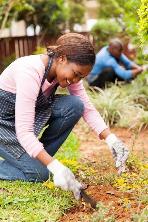 Ungt afrikanskt arbeta i trädgården för flicka royaltyfri foto
