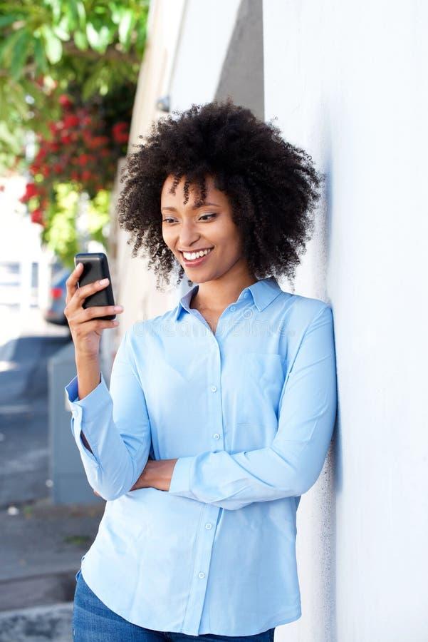 Ungt afrikanskt kvinnaanseende av en vägg som använder utomhus den smarta telefonen arkivfoto