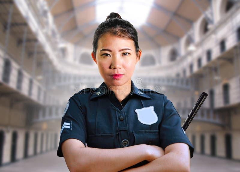 Ungt allvarligt och attraktivt asiatiskt amerikanskt vaktkvinnaanseende på likformign för polisen för korridor för tillståndsstra royaltyfri foto