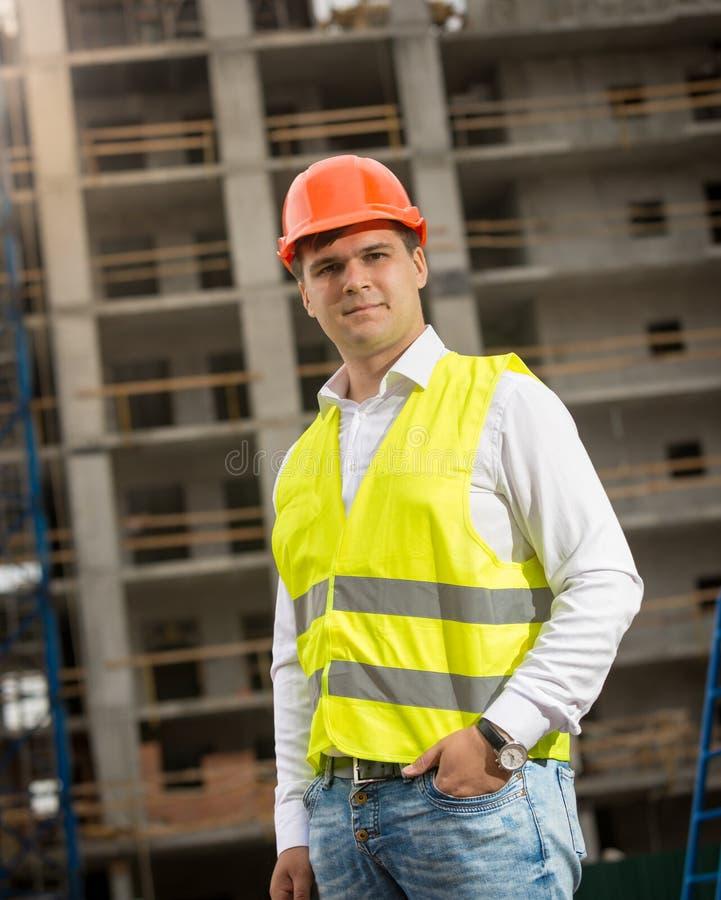Ungt anseende för konstruktionstekniker på byggnadsplatsen och lookin royaltyfria foton