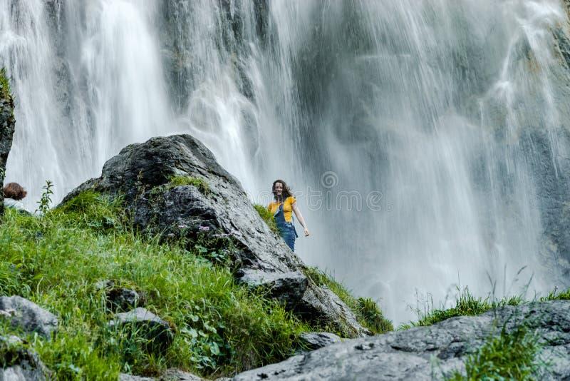 Ungt anseende för tonårs- flicka på den stora stenen nära vattenfallet royaltyfria bilder