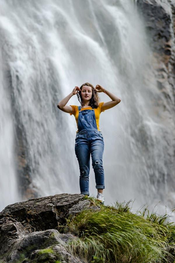 Ungt anseende för tonårs- flicka på den stora stenen nära vattenfallet royaltyfria foton