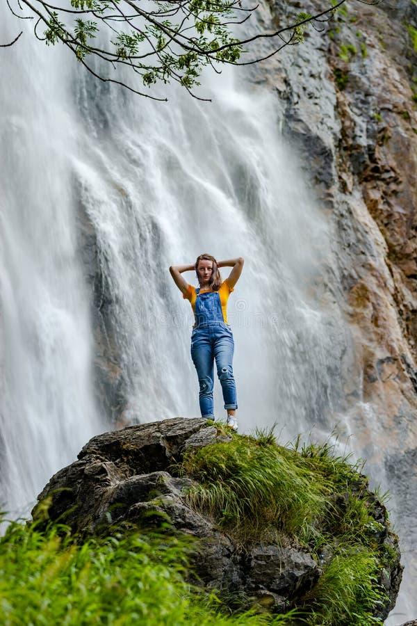 Ungt anseende för tonårs- flicka på den stora stenen nära vattenfallet arkivbilder