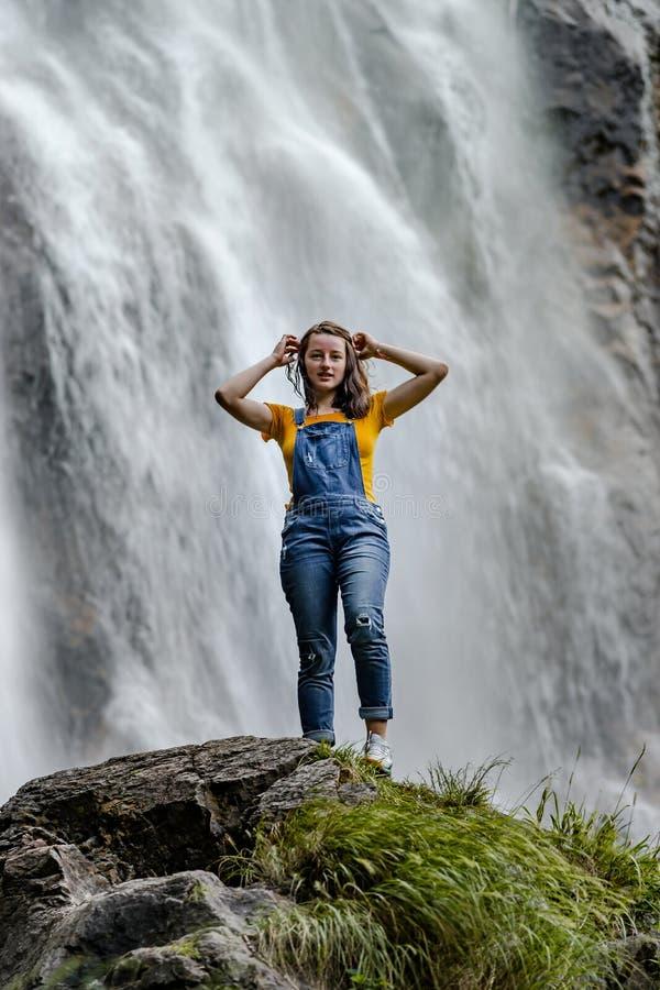 Ungt anseende för tonårs- flicka på den stora stenen nära vattenfallet arkivfoto