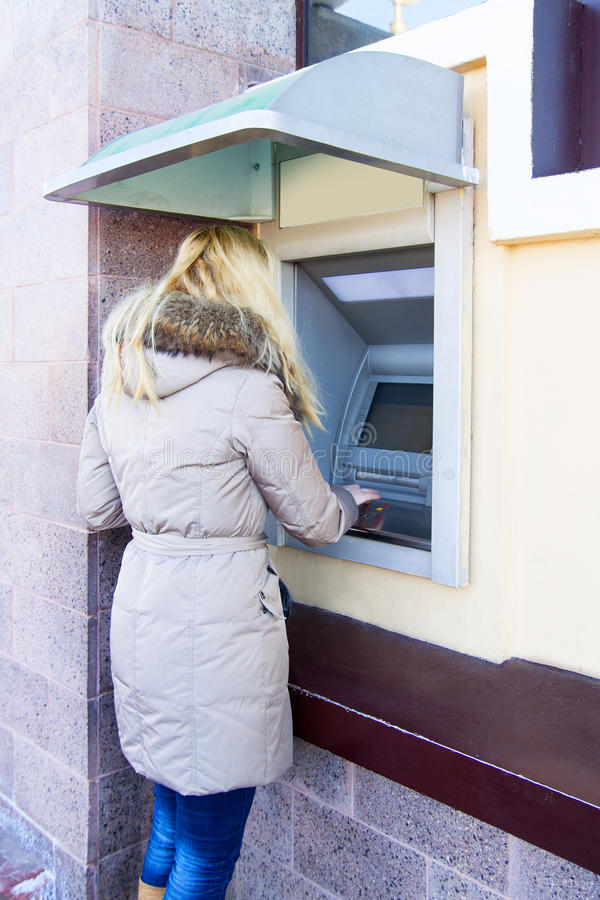 Ungt använda för kvinna packar ihop ATM arkivfoto
