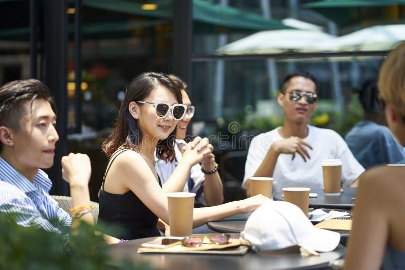 Ungt asiatiskt folk som kopplar av i coffee shop arkivbilder