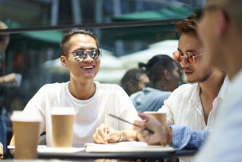 Ungt asiatiskt folk som kopplar av i coffee shop arkivbild