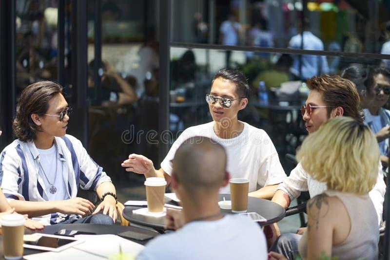 Ungt asiatiskt folk som kopplar av i coffee shop royaltyfria foton