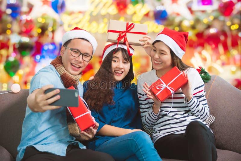 Ungt asiatiskt folk som tar fotoet vid mobiltelefonen i julparti arkivbilder