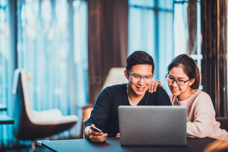 Ungt asiatiskt gift par som arbetar tillsammans genom att använda det hemmastadda eller moderna kontoret för bärbar dator med kop royaltyfri fotografi