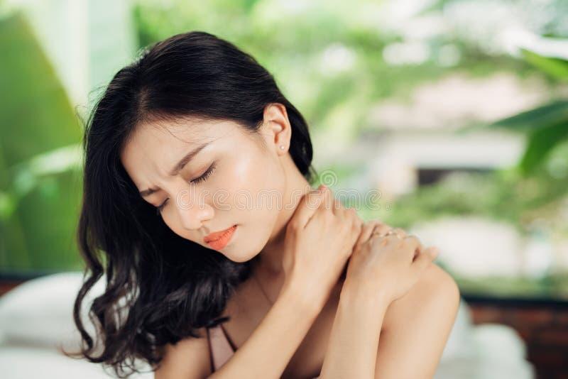 Ungt asiatiskt kvinnalidande från hals smärtar, medan sitta på säng royaltyfri foto