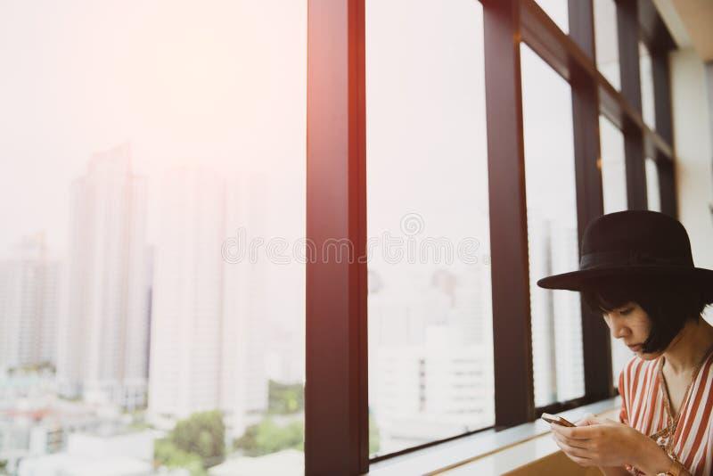 Ungt asiatiskt kvinnasammanträde i den höga byggnaden, genom att använda smartphonen royaltyfria bilder