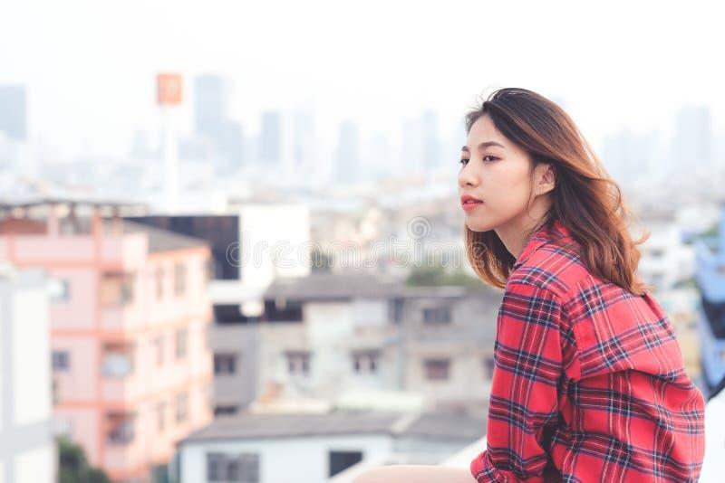 Ungt asiatiskt kvinnasammanträde och le på taket som är utomhus- i stads- stadsbakgrund, lycklig livsstil arkivbilder