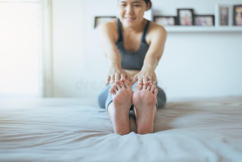 Ungt asiatiskt kvinnasammanträde på säng som öva göra yogaövningen, kvinnlig genomkörare, når att ha vaknat upp hemma fotografering för bildbyråer