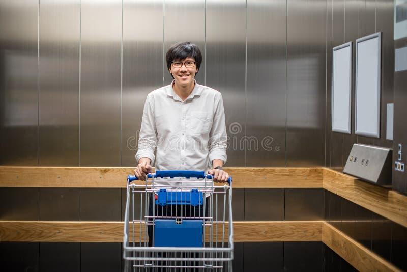 Ungt asiatiskt mananseende med spårvagnvagnen i elevator eller elevatior royaltyfria bilder