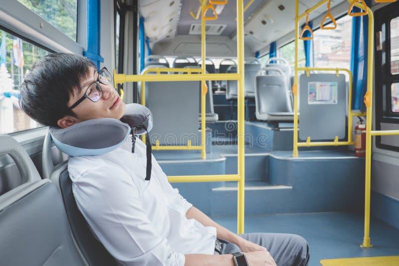 Ungt asiatiskt manhandelsresandesammanträde på en buss och sova med kudde-, transport-, turism- och vägturbegrepp arkivfoton