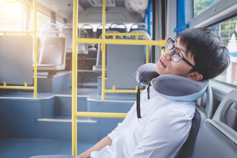 Ungt asiatiskt manhandelsresandesammanträde på en buss och sova med preventivpilleren royaltyfria foton