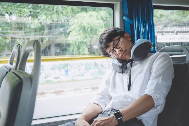 Ungt asiatiskt manhandelsresandesammantr?de p? en buss och sova med kudde-, transport-, turism- och v?gturbegrepp fotografering för bildbyråer