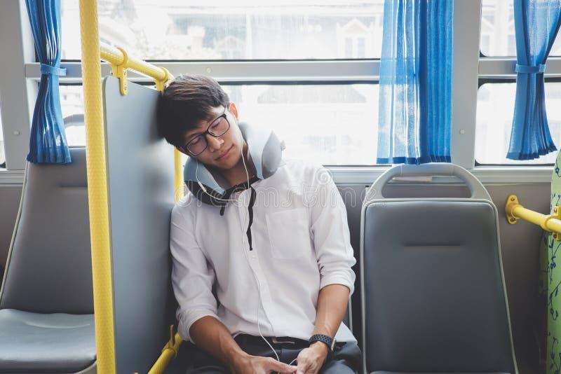 Ungt asiatiskt manhandelsresandesammantr?de p? en buss och sova med kudde-, transport-, turism- och v?gturbegrepp royaltyfri foto