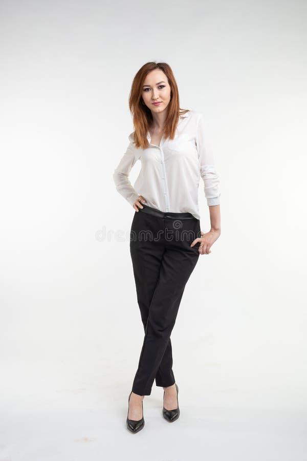 Ungt asiatiskt nätt slut för ung kvinna upp ståenden på vit bakgrund arkivbild