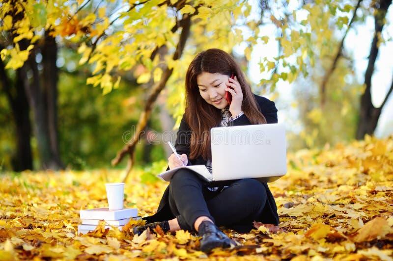 Ungt asiatiskt studera för kvinna/arbeta och tycka om höstdag royaltyfri bild