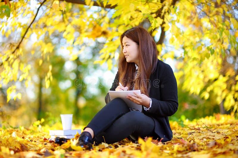 Ungt asiatiskt studera för kvinna/arbeta och tycka om solig höstdag royaltyfri foto