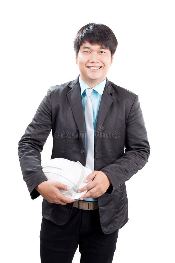 Ungt asiatiskt teknikmananseende och hållande säkerhetshjälm I royaltyfri bild