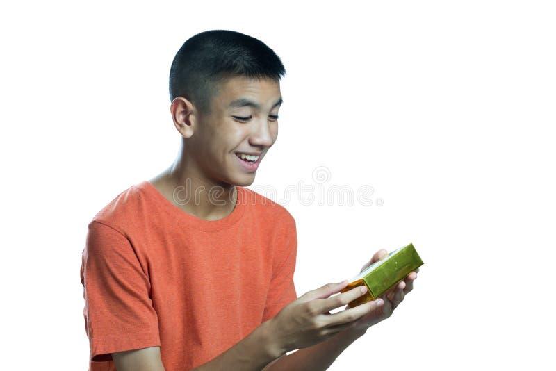 Ungt asiatiskt tonårigt lyckligt att få en gåva arkivfoton