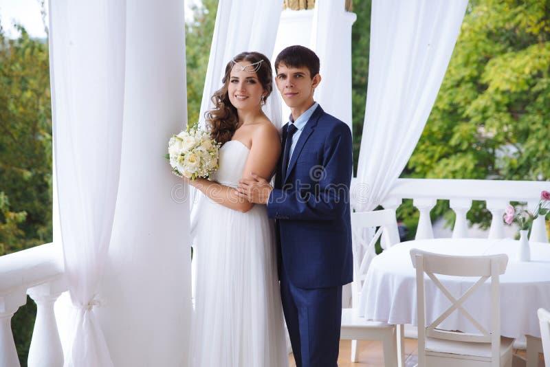 Ungt att gifta sig posera för gift par precis på terrassen, mannen kramar försiktigt hans fru vid skuldrorna royaltyfria bilder