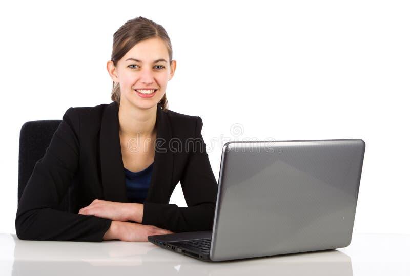 Ungt attraktivt affärskvinnasammanträde bak ett skrivbord royaltyfria bilder