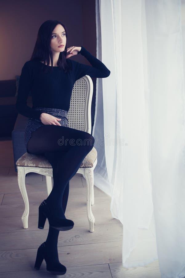 Ungt attraktivt brunettkvinnasammanträde på den gammalmodiga stolen fotografering för bildbyråer