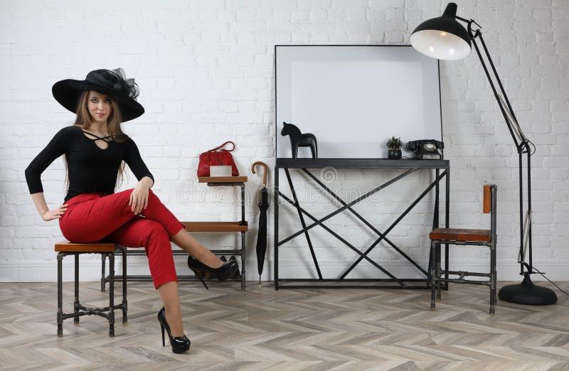 Ungt attraktivt flickasammanträde på en stol i studion arkivbilder