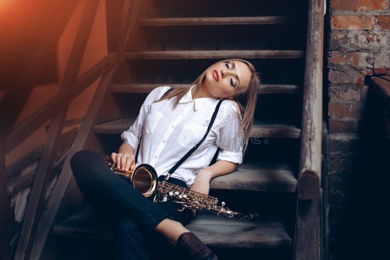 Ungt attraktivt flickasammanträde på moment i den vita skjortan med en utomhus- saxofon - Sexig ung kvinna med saxofonen som ser  royaltyfria foton