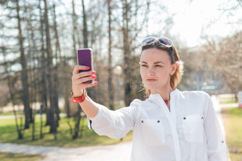 Ungt attraktivt foto för kvinnadanandeselfie på smartphonen arkivbild