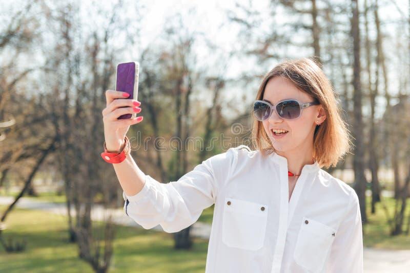 Ungt attraktivt foto för kvinnadanandeselfie på smartphonen arkivbilder