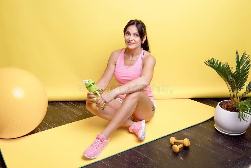 Ungt attraktivt idrotts- kvinnasammanträde på golvet på Teppich Matte Fitness efter aktivitet i idrottshallen royaltyfria foton