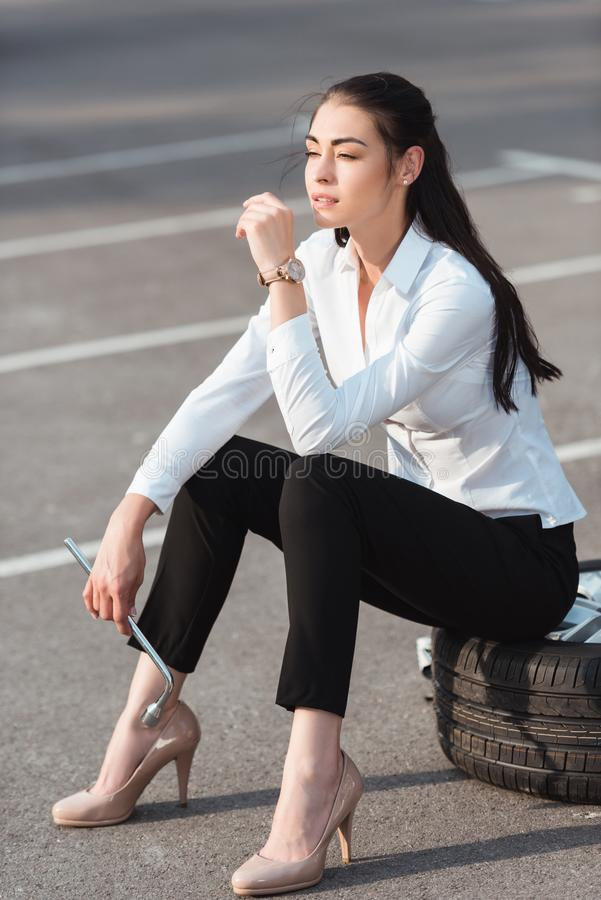 Ungt attraktivt kvinnasammanträde på bilgummihjulet med släpandeskiftnyckeln i hennes hand royaltyfria bilder