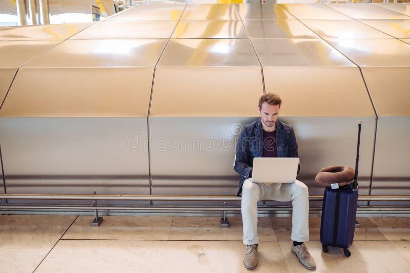 Ungt attraktivt mansammanträde på flygplatsen som arbetar med en lapto arkivfoton