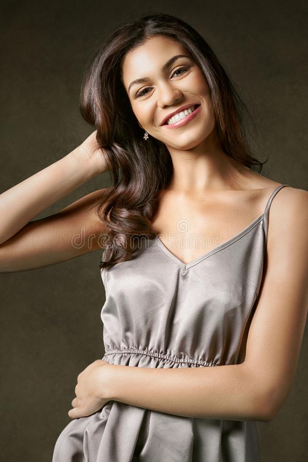 Ungt attraktivt och att le kvinnan i en silvernattklänning fotografering för bildbyråer