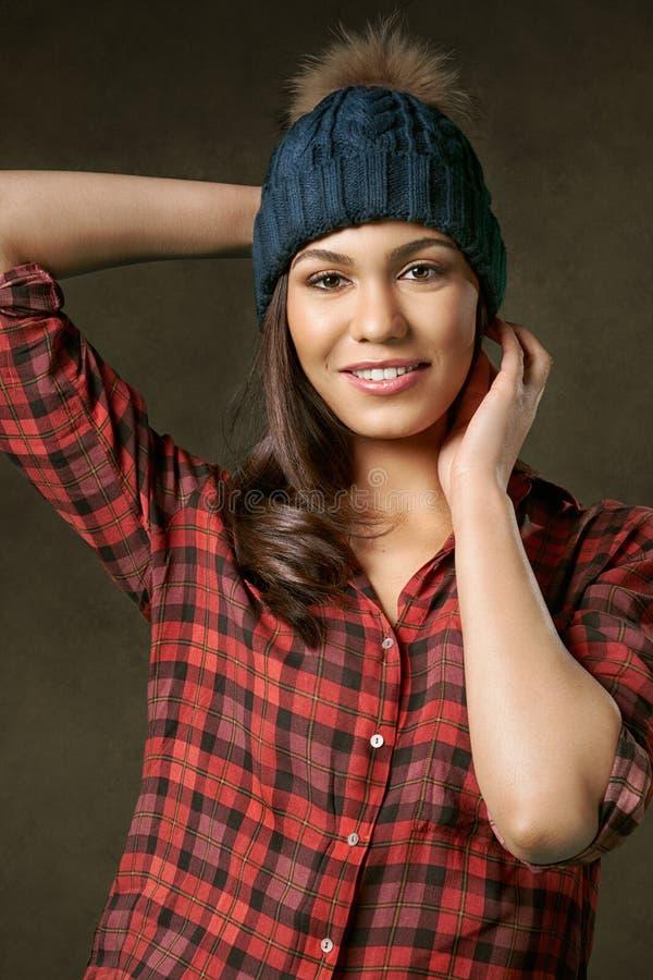 Ungt attraktivt och att le kvinnan som justerar en vinterhatt arkivfoton