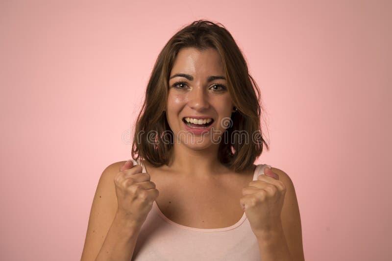 Ungt attraktivt och härligt le för kvinna som är upphetsat och som är lyckligt i vinnare och segergest royaltyfria foton